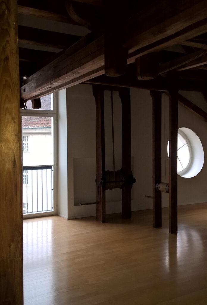 Parkett in einer Loft-Wohnung mit Holzstützen und rundem Brillenfenster.