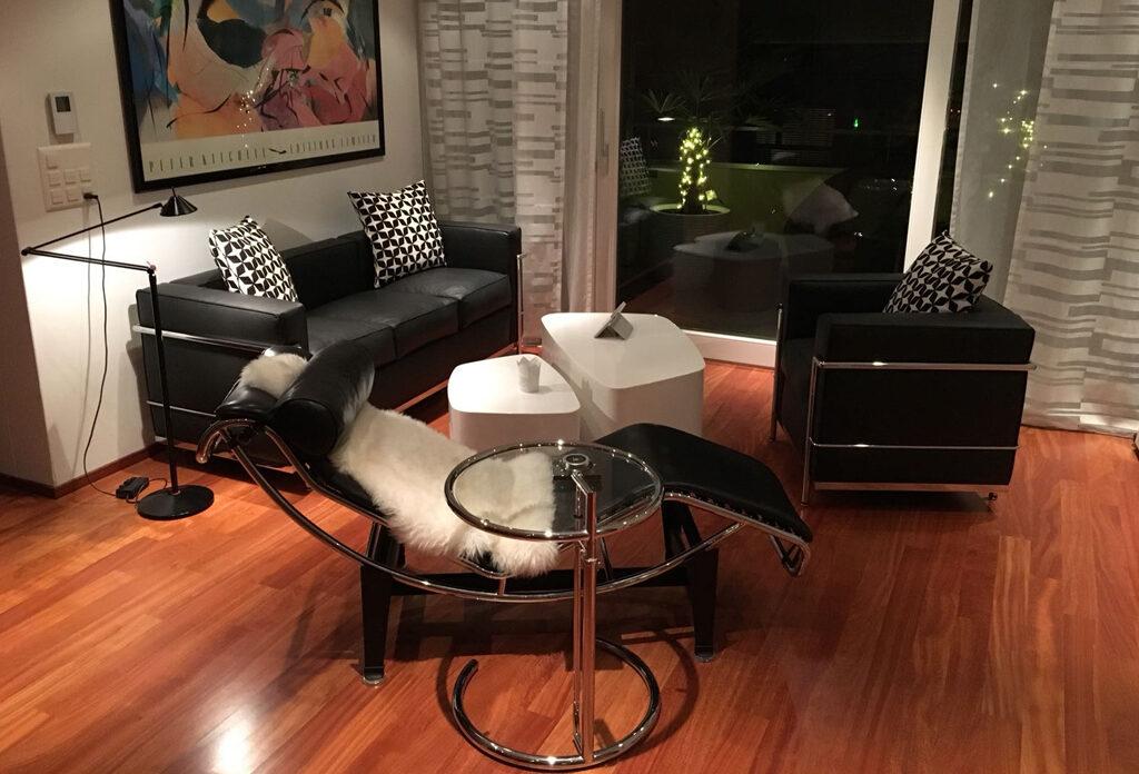 Ein dekoriertes Wohnzimmer mit schwarzem Ledersofa und Sessel, Liegestuhl, rundem Glastisch, weissem Couchtisch, Vorhängen, Beleuchtung und dem Spiegelbild eines Balkonfensters.