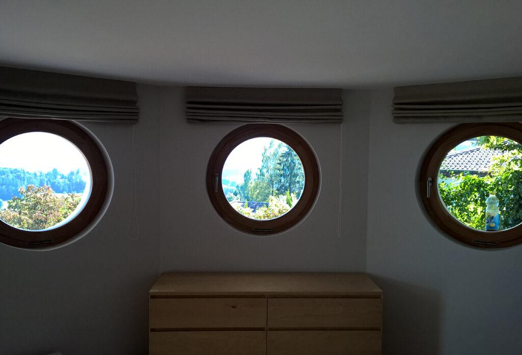 Jalousien rollten über drei Bullaugenfenster mit Blick auf Bäume.
