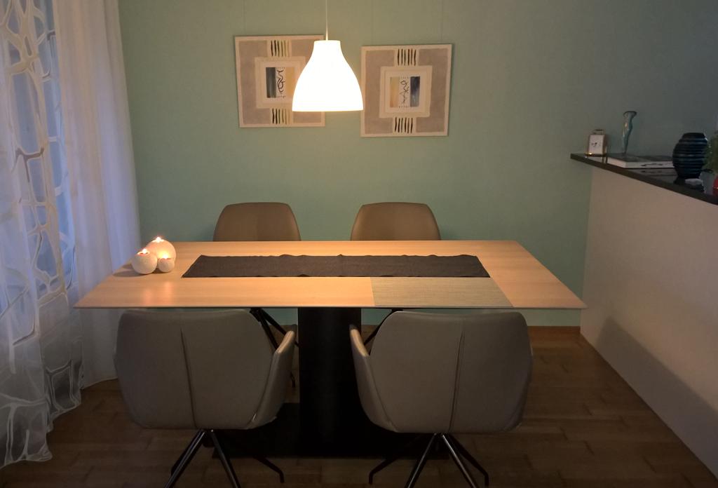 Ein Esstisch und Stühle mit Deckenleuchte, Kerzen, durchsichtigen Fenstervorhängen, Kunstwerken und durch eine dekorierte Frühstückstheke von der Küche getrennt.