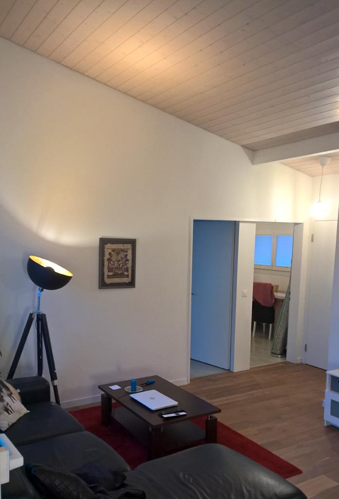 Ein Loft-Wohnzimmer mit Spotlampenbeleuchtung, schwarzem Ledersofa und Couchtisch.