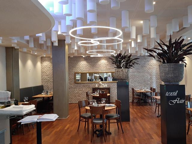 Der renovierte Hauptspeisebereich eines Restaurants zeigt neue Pflanzen, Polster, Wandspiegel, Deckenleuchten und Schalldämpfer.