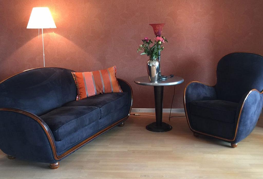 Neue Tapete mit blauen Möbeln, Lampen und Blumendekorationen